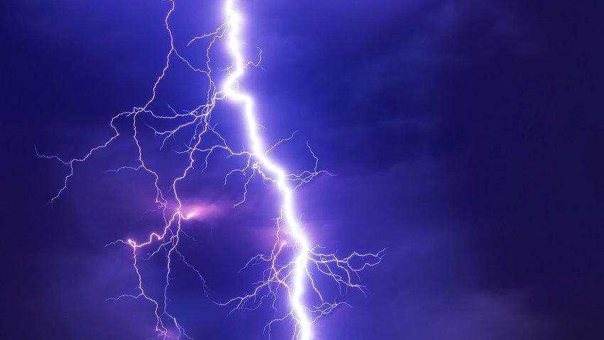 Lightning bolt brightly lit up against dark clouds