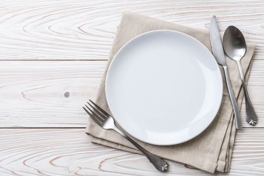 Empty white plate with silverware on table