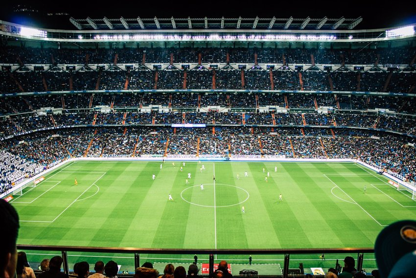 Soccer game being played in a large stadium at night