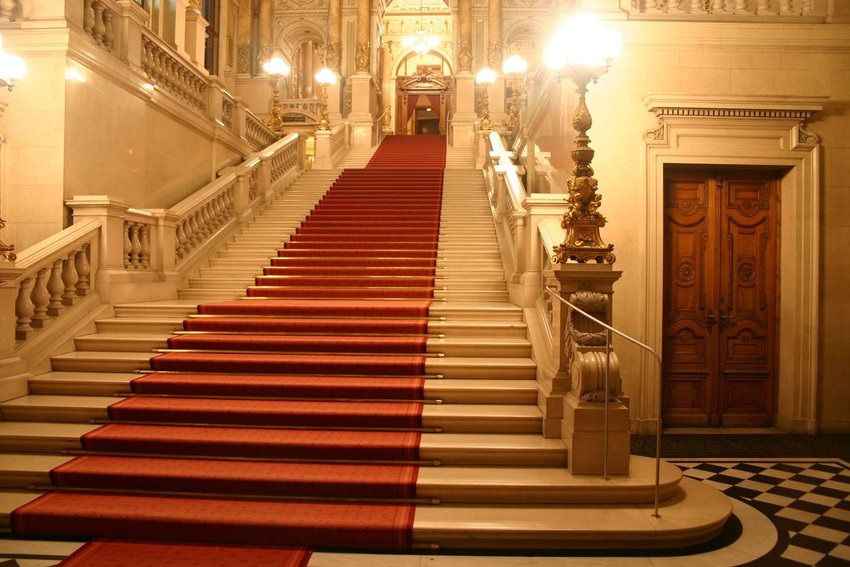 Large patrician staircase with iconic red carpet, with soft lighting and architecture