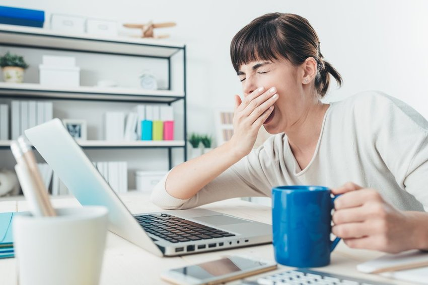 Tired woman sitting at laptop and yawning