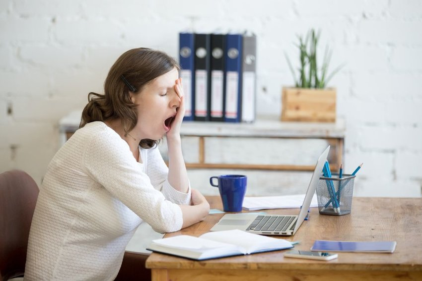 Woman in white sitting at laptop computer and yawning
