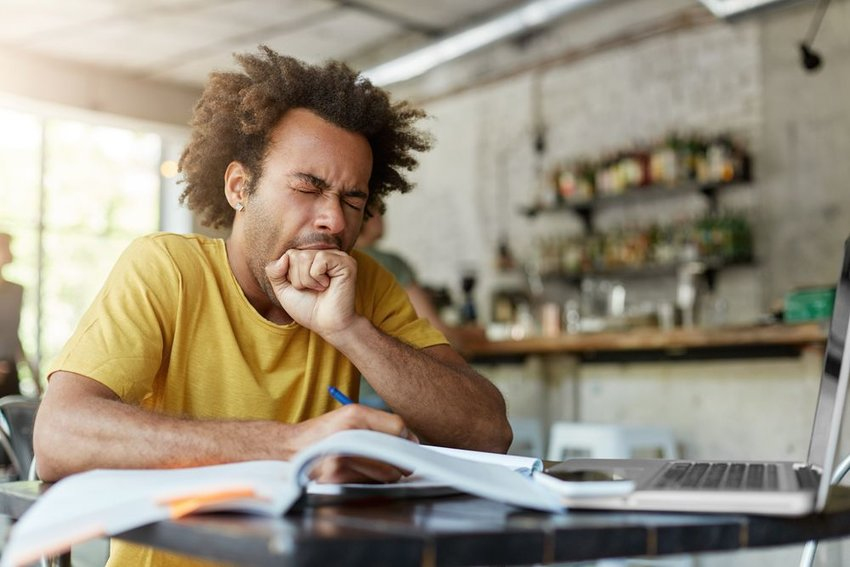 Man sitting at desk in front of books, yawning with hand over mouth