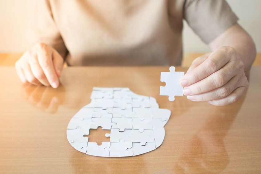 Person sitting at table placing a puzzle piece into a puzzle shape of human head