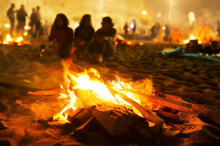 Group of people on sandy beach create several small campfires in celebration
