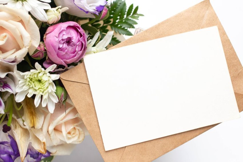 Card and envelope beside large bouquet of flowers