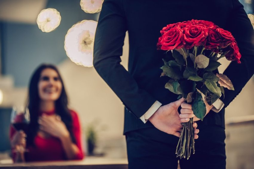 Man with large bouquet of roses behind his back about to speak to woman at table