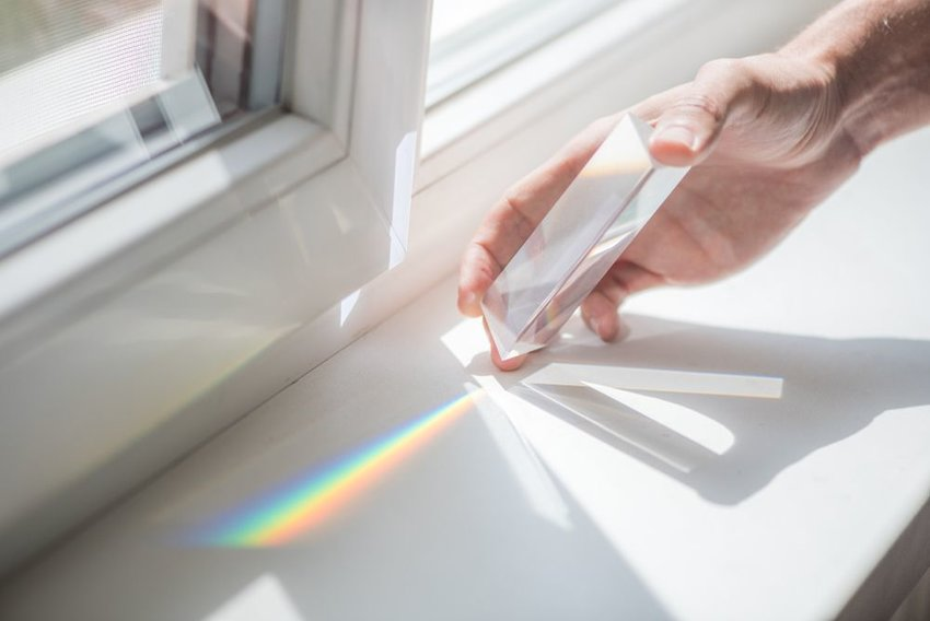 Person's hand holding prism against light, showing rainbow colors