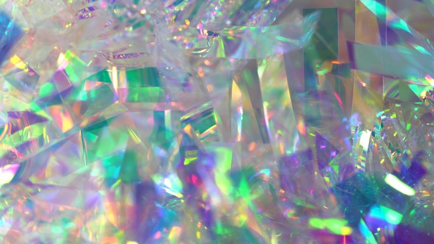 Up close view of crumpled foil refracting light in various colors of the rainbow