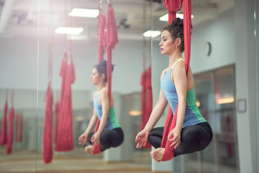 Woman hanging from anti-gravity yoga bands performing meditation
