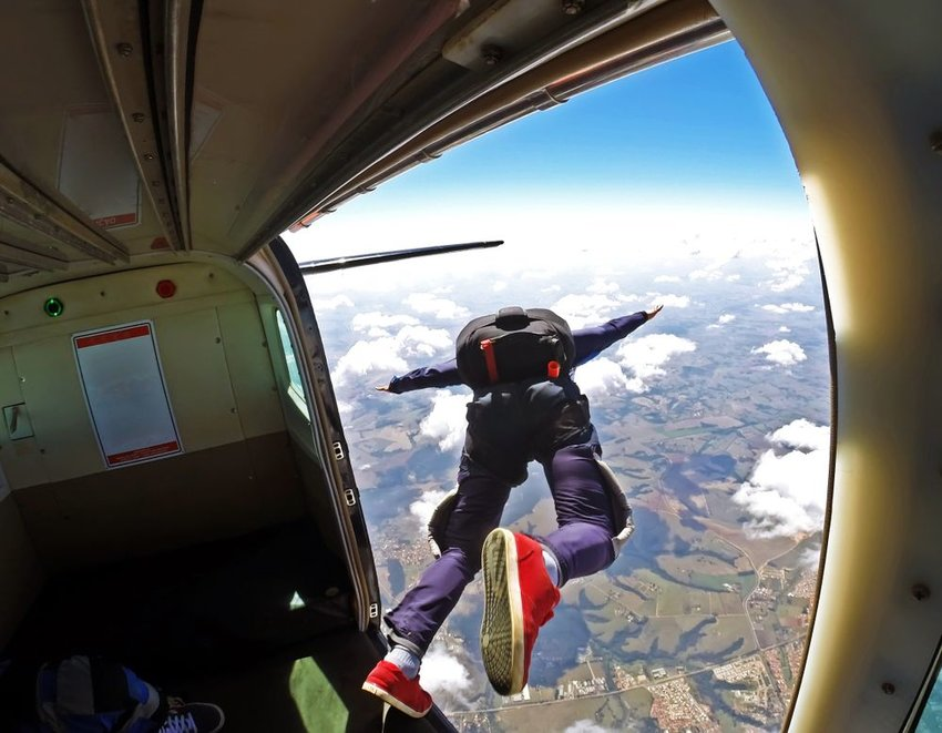 Person diving out of airplane, prepared to skydive to the ground below