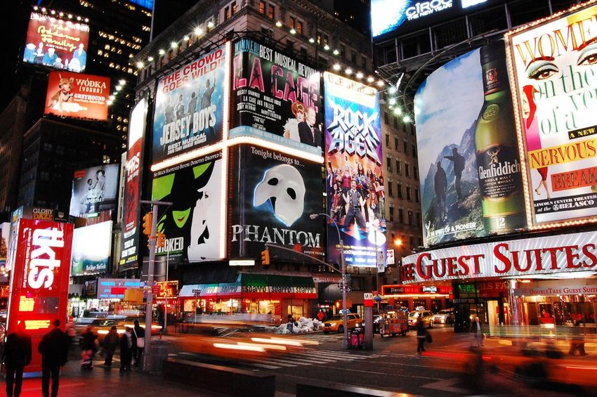 Broadway in New York, showing huge signs for stage plays and people walking streets at night