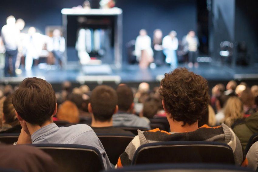 People in crowded theater watching performers on stage