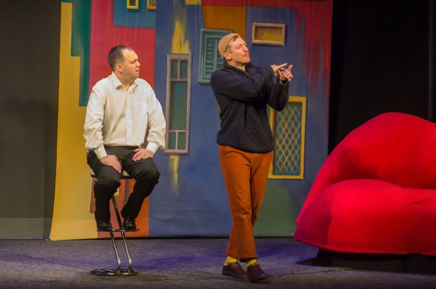 Performers on small theater stage act out a play with colorful set decor