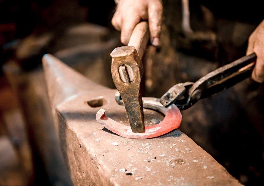 Blacksmith holding tongs and hammer, pressing horseshoe into shape