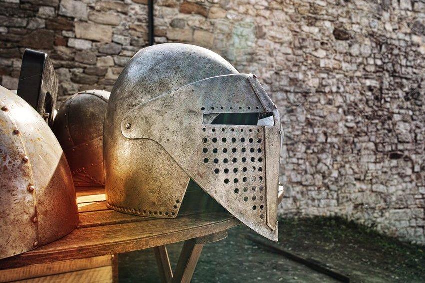 Traditional iron knight's helmet resting on bench near a stony castle wall