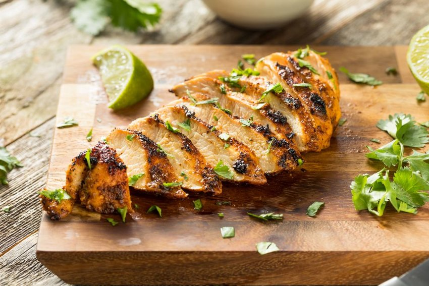 Wedge of roasted chicken on wooden plank garnished with fresh green cilantro