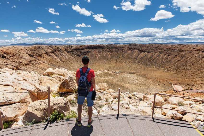 Tourist standing near large crater in the earth, Winslow, Arizona