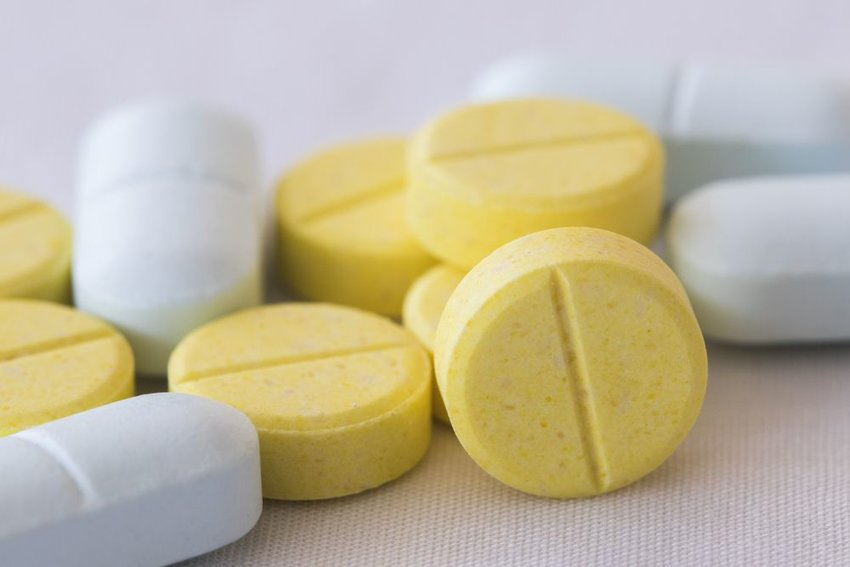Up close view of yellow and white medicinal pills on plain white table