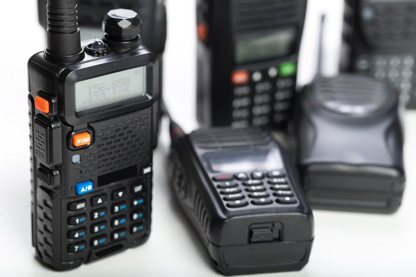 Stack of two-way radio devices showing transmitters and buttons