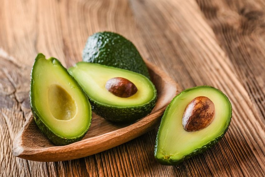 Several fresh green avocados sliced open on a rustic wooden table