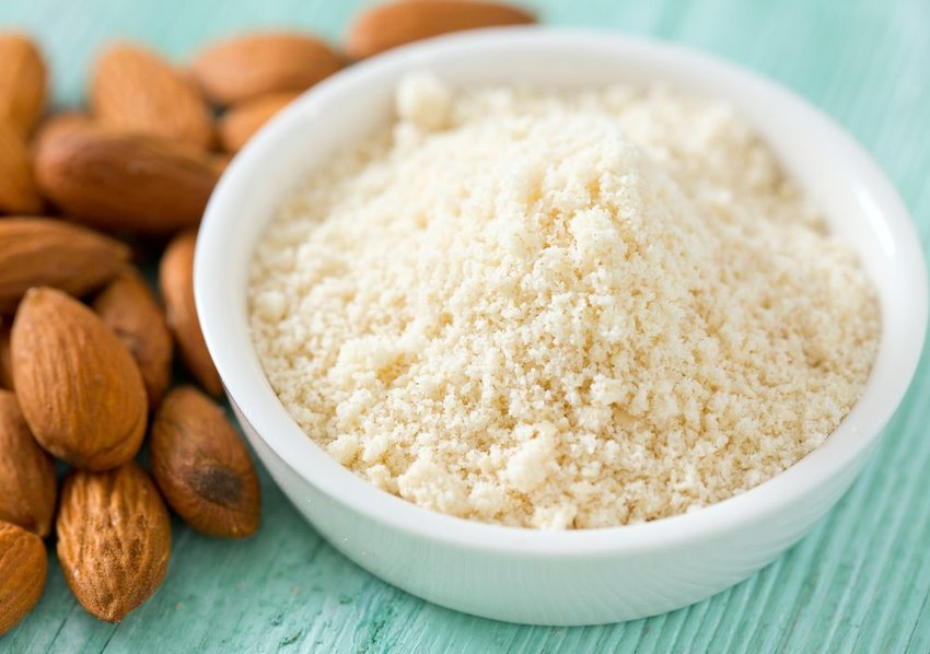 Bowl of finely ground almond powder sitting beside several whole almonds