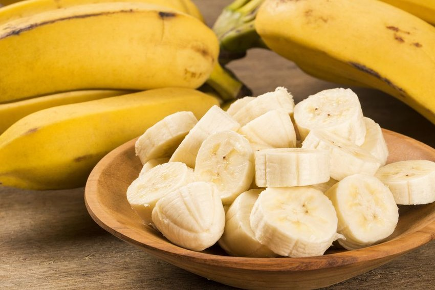 Bowl of sliced bananas sitting beside several large whole bananas