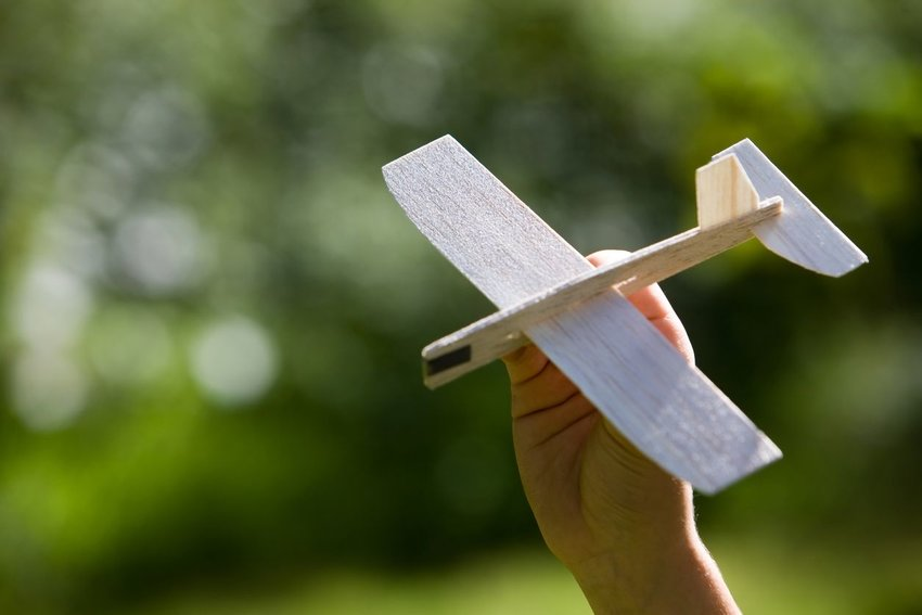 Child holding balsa wood airplane against a blurry background