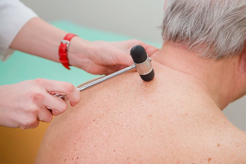 Man at doctor with rubber mallet placed near the top of spinal cord