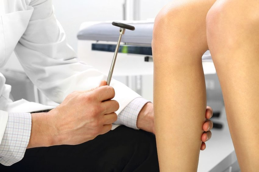 Woman at doctor appointment, showing rubber mallet hit against knee