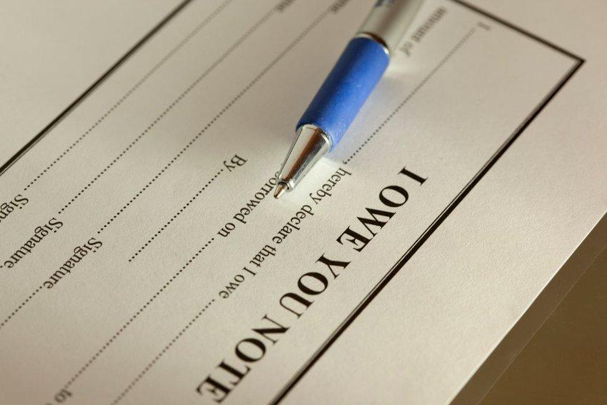 IOU promissory note resting under blue pen