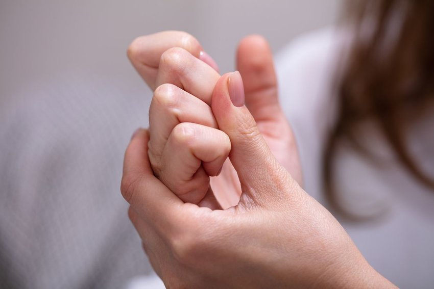 Woman holding hands together showing bent knuckles