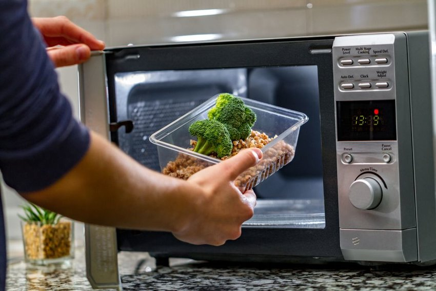 Man placing tray of leftovers into a microwave oven for reheating