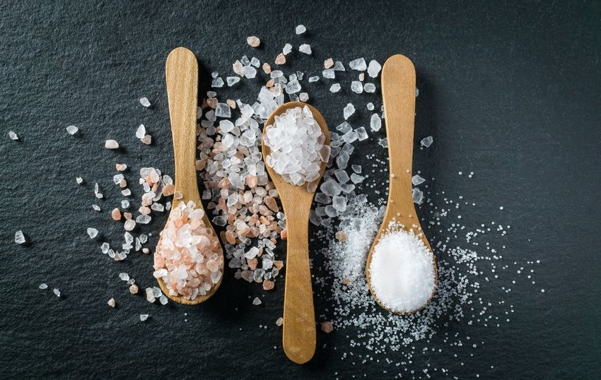 Wooden spoons holding white salts of various coarseness