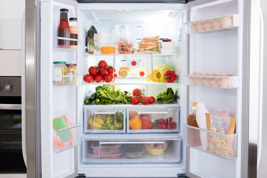 Open refrigerator with various foods and fresh vegetables contained within