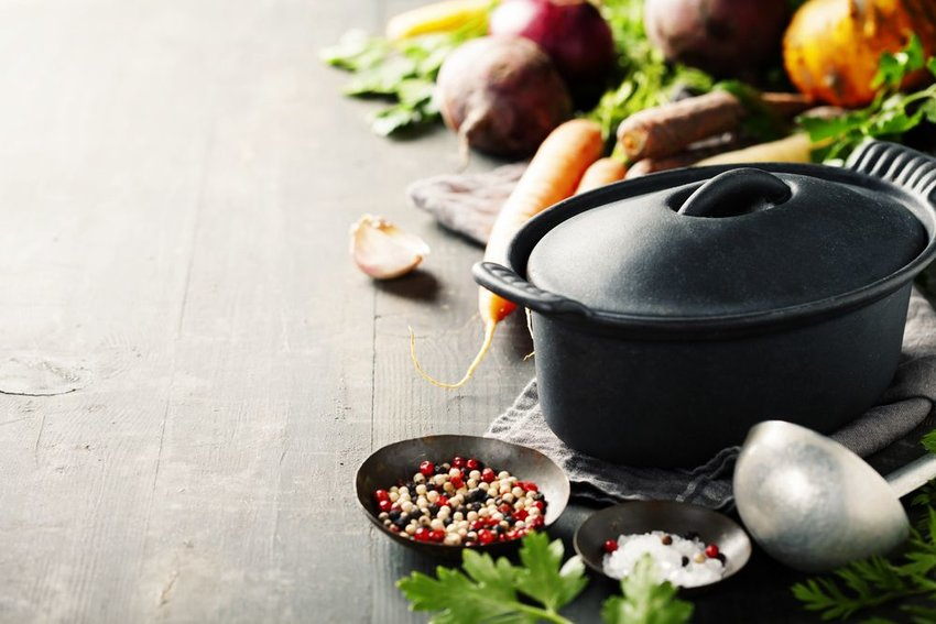 Iron cooking pot with various foods placed on a wooden table