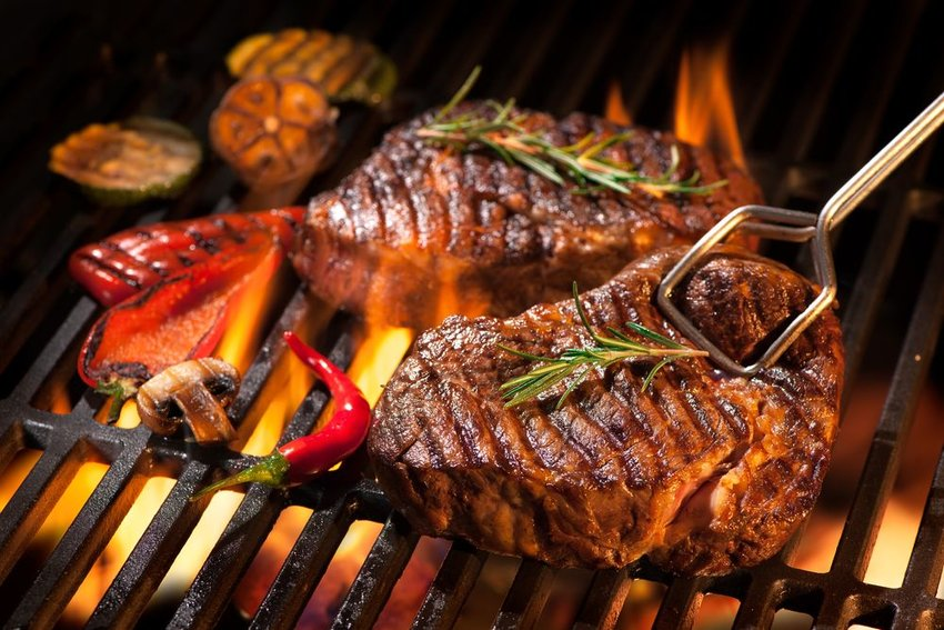 Up close view of meat and vegetables placed on grill, cooking over open flame