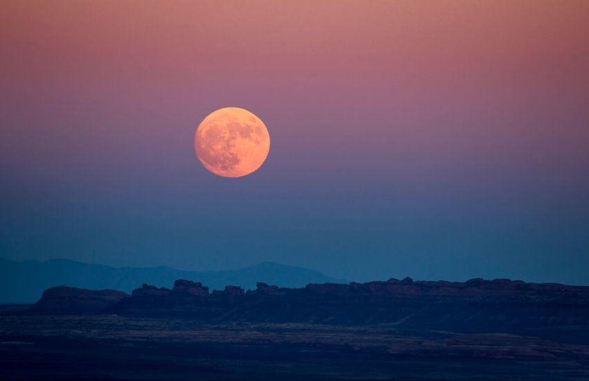 Rising full moon in a desolate desert landscape