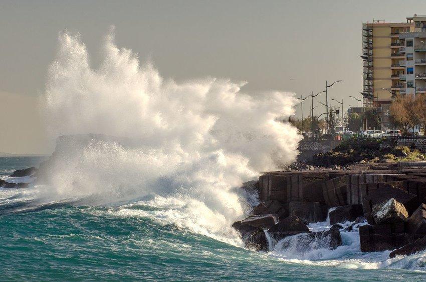 Big wave crashing over street