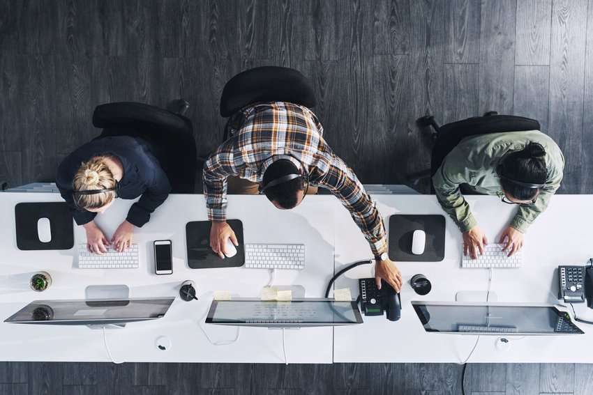 Three people working at their desks from above