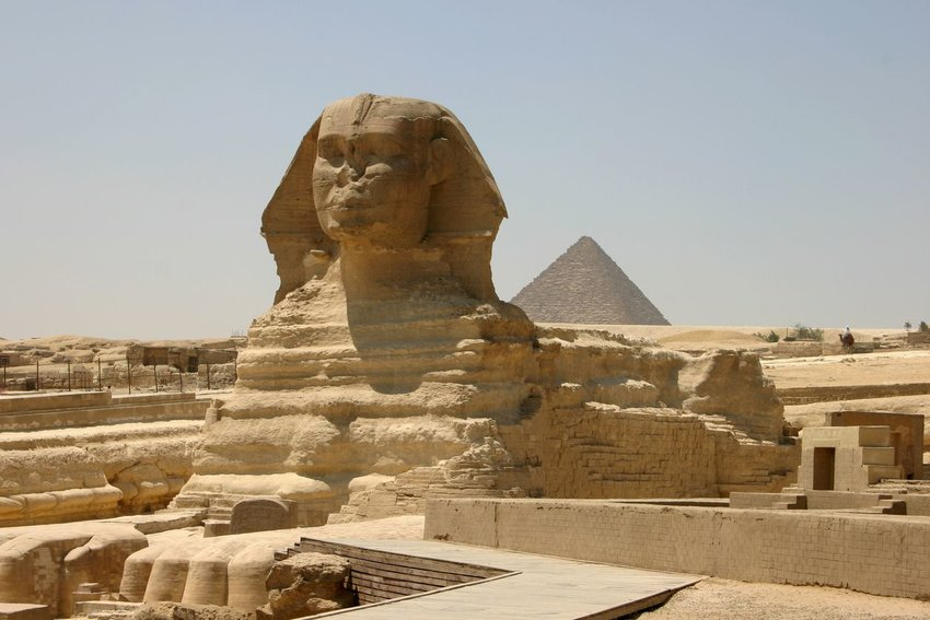 Sphinx statue with a pyramid in the background