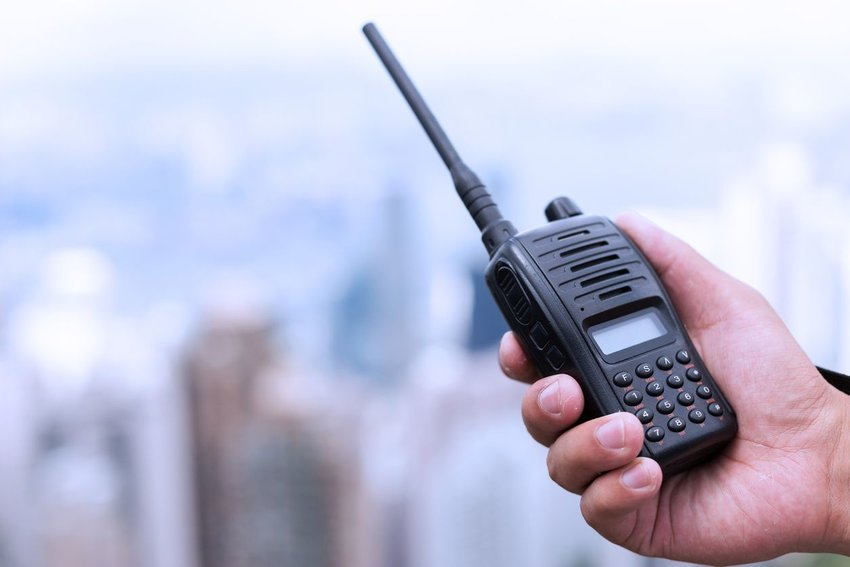 Small, black walkie talkie in someones hand