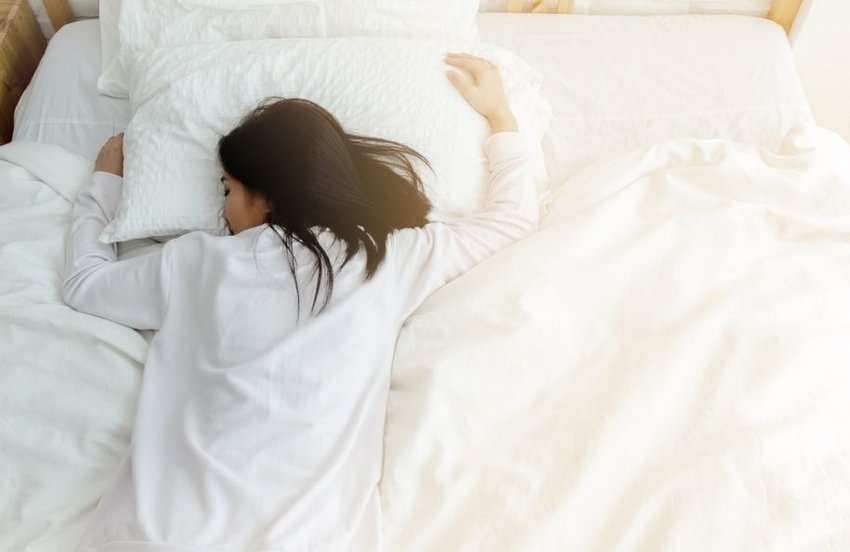 Person sleeping on stomach on big, white bed