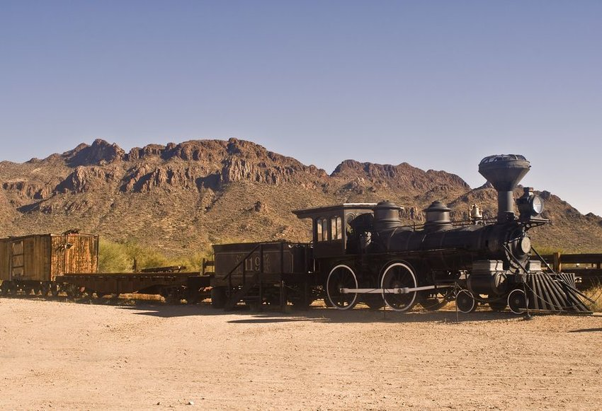 Old train in desert with rocky hills in background
