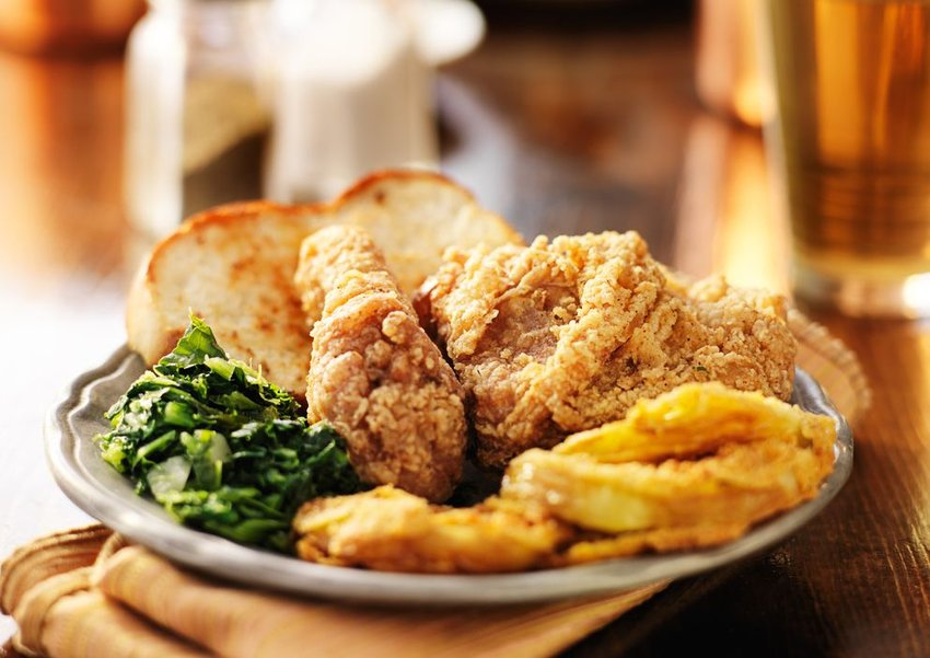 Plate of baked chicken, toast, chips and greens
