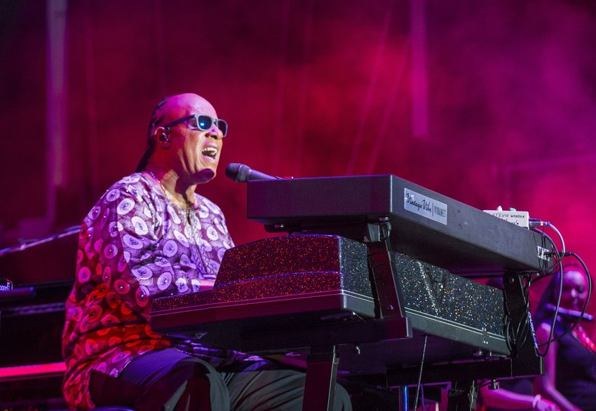 Musician Stevie Wonder playing the keyboard and singing on stage