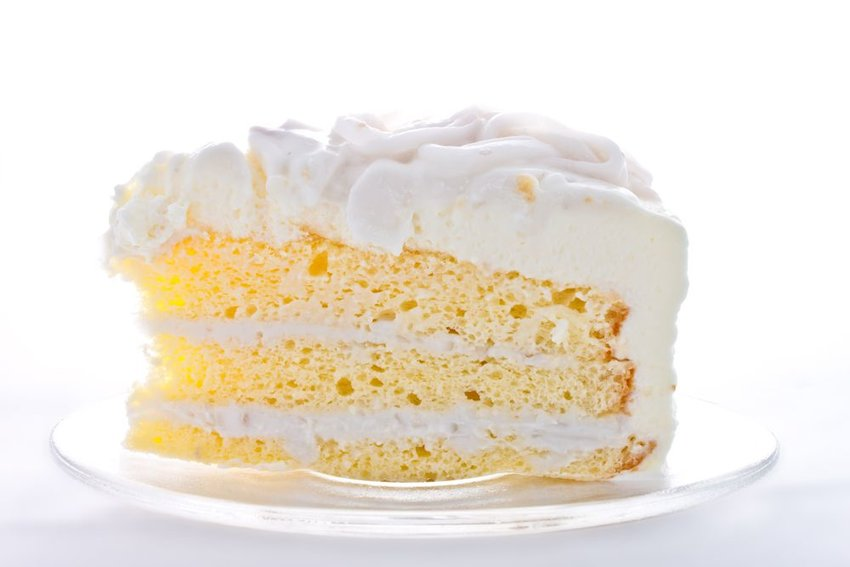 Piece of white vanilla cake on white plate with white background