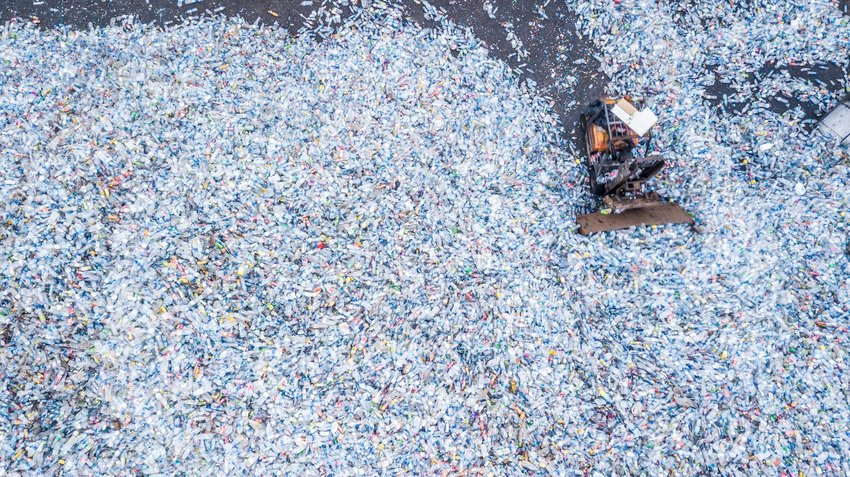 Aerial view of large bulldozer moving huge piles of plastic bottles in a landfill