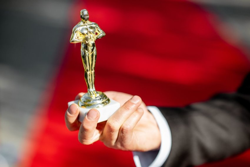Person holding out an Oscars trophy with red carpet in background