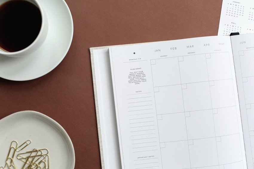 Flat lay of calendar with cup of coffee and paper clips